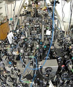 Reloj Compton. Espejos y lentes en este banco óptico preparan seis rayos láser para capturar átomos fríos en el interferómetro de átomos (en la parte trasera). (Damon Inglés / UC Berkeley)